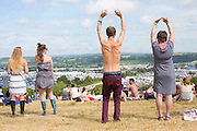 The sun continues to shine on the second day of Glastonbury Festival after it opened it's gates yesterday for the early arrivals. Approximately 170,000 revellers are set to turn up to the festival which is hosting a number of headliners including Kanye West and Alt J. <br /> Pictured: A festival goer (right) enjoys a free yoga lesson overlooking the festival ground.