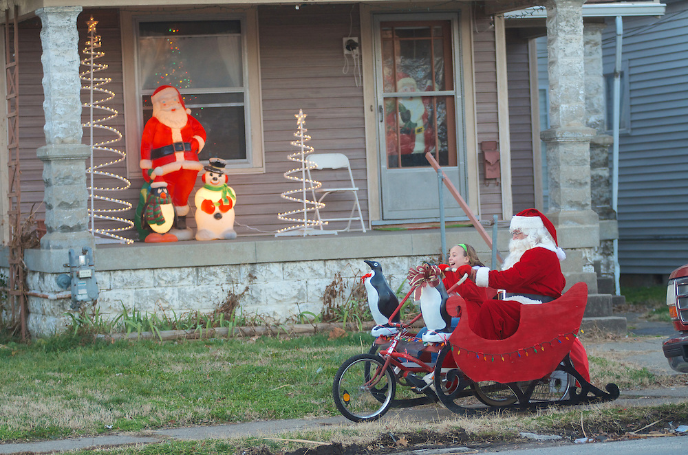 Dennis Osborne, dressed as Santa, takes his granddaughter Liliana Osborne, 9, for a ride down Shelby Street in the sleigh he built out of a 1970's tandem bicycle   from Arizona with solar Christmas lights and two penguins on the front. (Photo by Brian Bohannon)