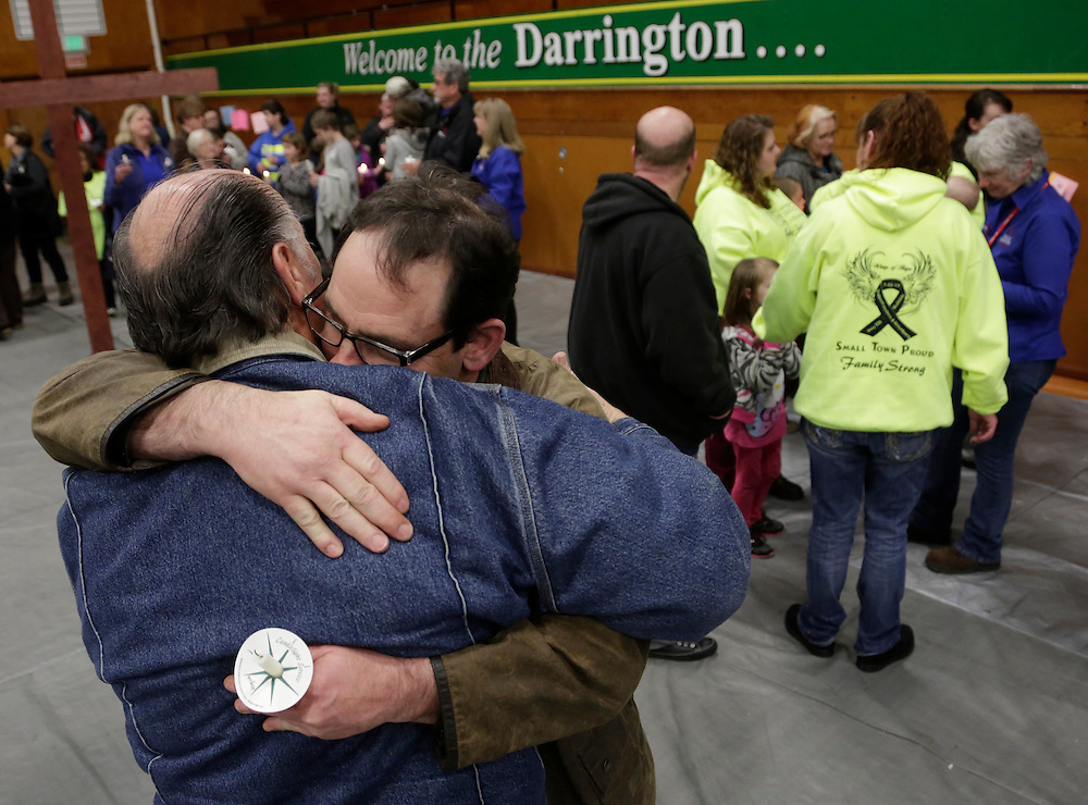 Darrington Mayor Dan Rankin (2nd L) and Pastor Jim Alexander (L) embrace following a candlelight vigil at the Community Center in Darrington, Washington April 5, 2014. Recovery efforts have been hampered by rain creating treacherous conditions and raising the risk of further slides and flash floods. More rain and runoffs of melting mountain snow are forecast, with a quarter of an inch (6 mm) of precipitation expected on Sunday, before a two-week stretch of warm weather arrives on Monday which officials said will aid search efforts. REUTERS/Jason Redmond (UNITED STATES)