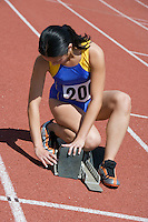Female athlete stetting up starting block