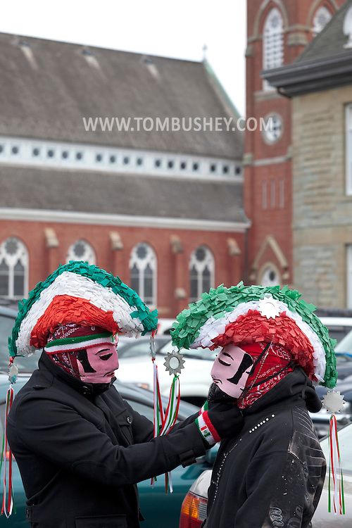 Middletown, New York - A man adjusts another man's mask outside St. Joseph's Church before marching through the city during the festival of Nuestra Senora de Guadalupe on Sunday, Dec. 9, 2012.