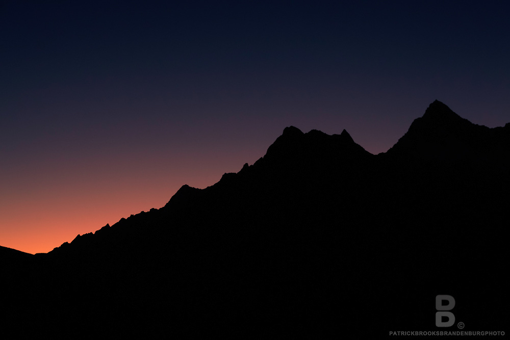 Silhouette of black ridged peaks lining down a sunset skyline in the Cordillera Blanca of the Andes Mountains in Peru. 8.15.11