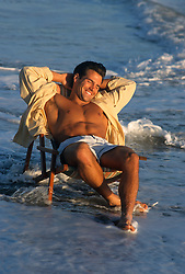 Good Looking Man Reclining In A Lounge Chair In The Ocean
