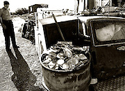 Bratislava, Slovakia (16/08/2006).Jano 66 stands outside his makeshift home in front of an old carand a drum of scrap metal. Jano makes his living from scrap metal and the drum of old tins will make him enough money to feed his family for three days.   .**Heavy Metal Lifestyle
