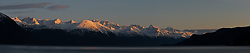 DIGITAL COMPOSITE PANORAMA (multiple overlapping images stitched together): The final rays of the setting sun at sunset bath the tops of the mountains of along the Chilkoot Inlet of the Lynn Canal taken  just outside Haines, Alaska.