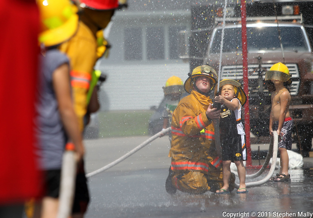 Brennan Snitkey (right), 5, and his father, Walker Volunteer Firefighter Shawn Snitkey, both of Cedar Rapids, participate in the Waterball event at the Walker Pickle Days in Walker on Saturday, July 30, 2011. Activities included a 5K run/walk, kid's fun run, horseshoe tournament, craft show, backyard games tournament, parade, and fireworks.
