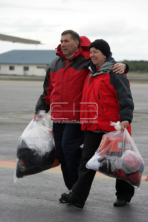 """25th November 2007, Punta Arenas, Chile. Survivors from the shipwrecked Antarctic vessel M/S Explorer arrive at Punta Arenas by military aircraft. 154 tourists and crew had spent the night on King George Island after their ship struck an iceberg and sank approximately 120km (75 miles) north of the Antarctic Peninsula. After several hours bobbing in small lifeboats surrounded by floating sheets of ice, they were plucked to safety by the Norwegian cruise ship, the Nordnorge. The """"Spirit of Shackleton"""" 19-day cruise through the Drake Passage, cost from around $8,000 (£3,900) per cabin. Pictured the second group of passengers arriving at Punta Arenas airport..PHOTO © JOHN CHAPPLE / REBEL IMAGES.john@chapple.biz   www.chapple.biz"""