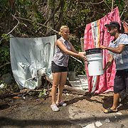 OCTOBER 25 - UTUADO, PUERTO RICO - <br /> Paola Bernacett, 19, and neighbor Daniel Santos, 27, using a stream of water coming from a mountain in Utuado to wash clothes.<br /> (Photo by Angel Valentin/Freelance)
