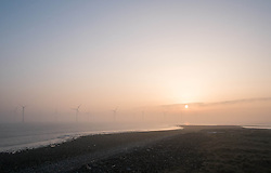 © Licensed to London News Pictures. 13/03/2014<br /> <br /> South Gare, Teesside, England, UK<br /> <br /> The sun rises through the smoke from industrial works as it drifts through an offshore wind farm in an area known as South Gare at the mouth of the River Tees on Teesside.<br /> <br /> Photo credit : Ian Forsyth/LNP