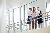 Businesswomen discussing over paperwork against railing