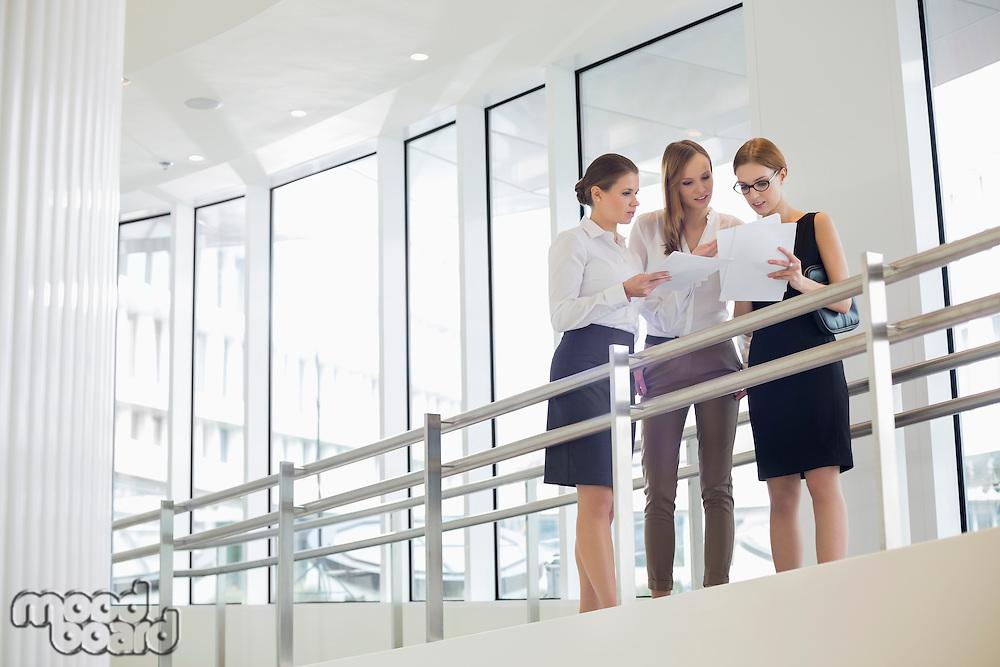 Businesswomen discussing over paperwork against railing