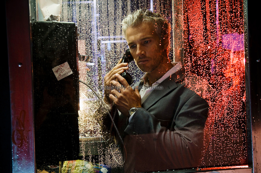 A man makes a phone call in a phone booth at night in the rain.