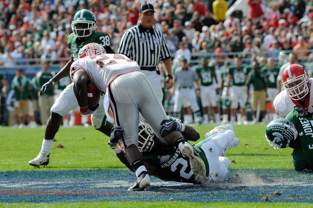 January 1, 2009: Knowshon Moreno of the Georgia Bulldogs is tackled by Otis Wiley of the Michigan State Spartans during the NCAA football game between the Michigan State Spartans and the Georgia Bulldogs in the Capital One Bowl. The Spartans were leading the Bulldogs 6-3 at halftime.