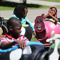 Cloey Montgomery waits for the train to fill up so she and others can enjoy a ride around the Hillsdale Aprtment complex as part of their summer kick-off on Thursday.