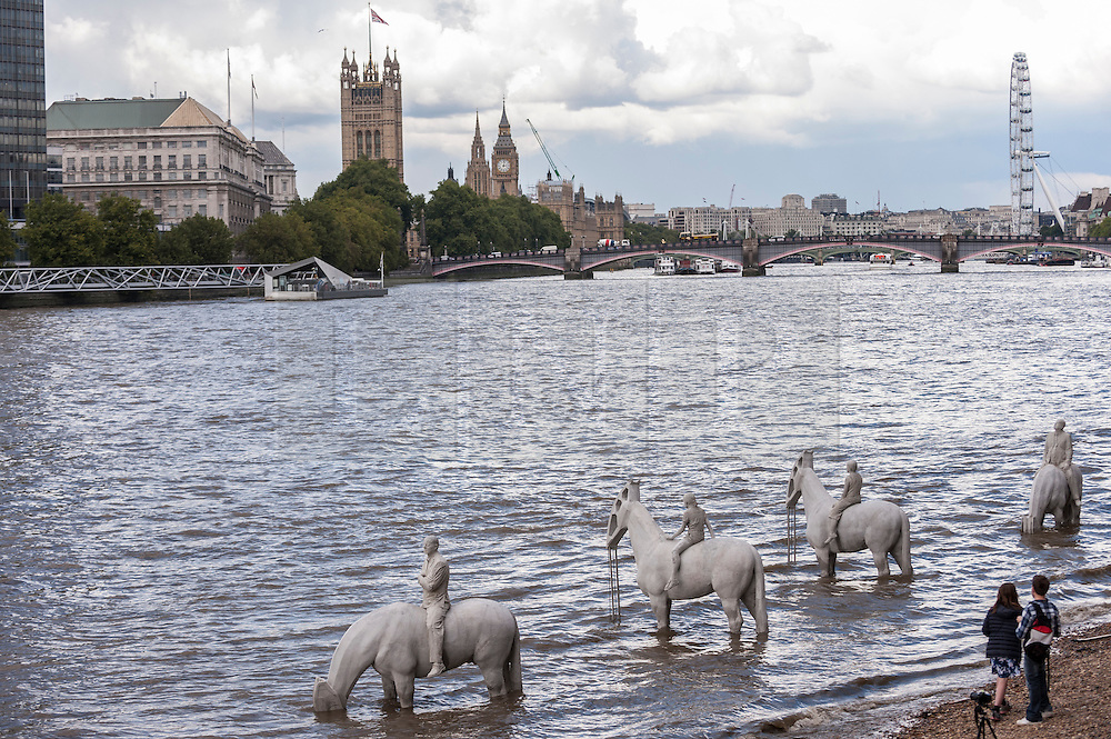 "© Licensed to London News Pictures. 02/09/2015 London, UK. A couple admire the art installation entitled ""The Rising Tide"" (comprising four horse-riders on horses with petroleum pumps for heads) by the underwater eco-sculptor Jason deCaires Taylor, which stands on the foreshore of the River Thames in Vauxhall and is revealed with each low tide.  The installation aims to question man's reliance on fossil fuels and is part of this year's Totally Thames festival. Photo credit : Stephen Chung/LNP"