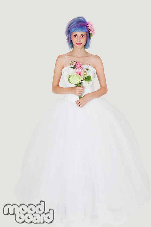 Portrait of beautiful young woman in wedding outfit with dyed hair against gray background