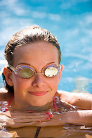 young girl in a swimming pool with her goggles on with a reflection in the goggles.Model Released