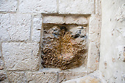 Israel, Jerusalem, Via Dolorosa, Station No. V Simon of Cyrene carries the cross. Jesus stumbles and leans on the wall his hand print is believed to be in the rock