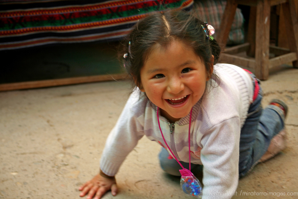 Americas, South America, Peru, Pisac. Happy little girl plays on the floor of the market.