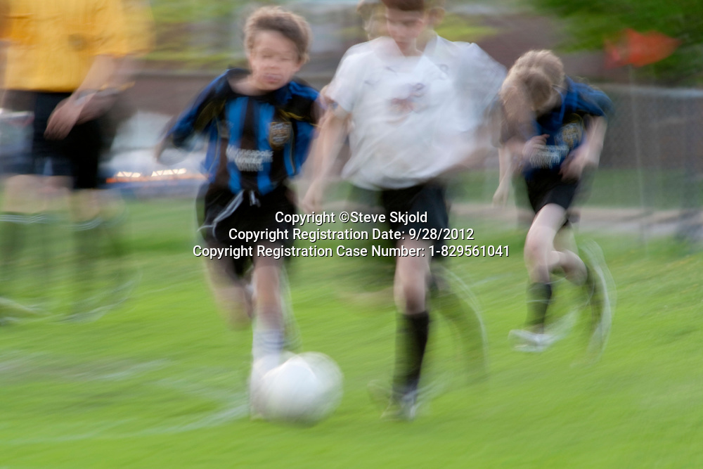 Boys age 10 playing soccer game blurred to show action. Monroe Memorial Park St Paul Minnesota MN USA
