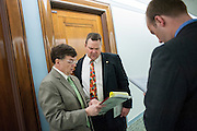 Montana Senator Jon Tester (D) takes a meeting in the hallway outside of an armed services budget hearing on Capitol Hill.