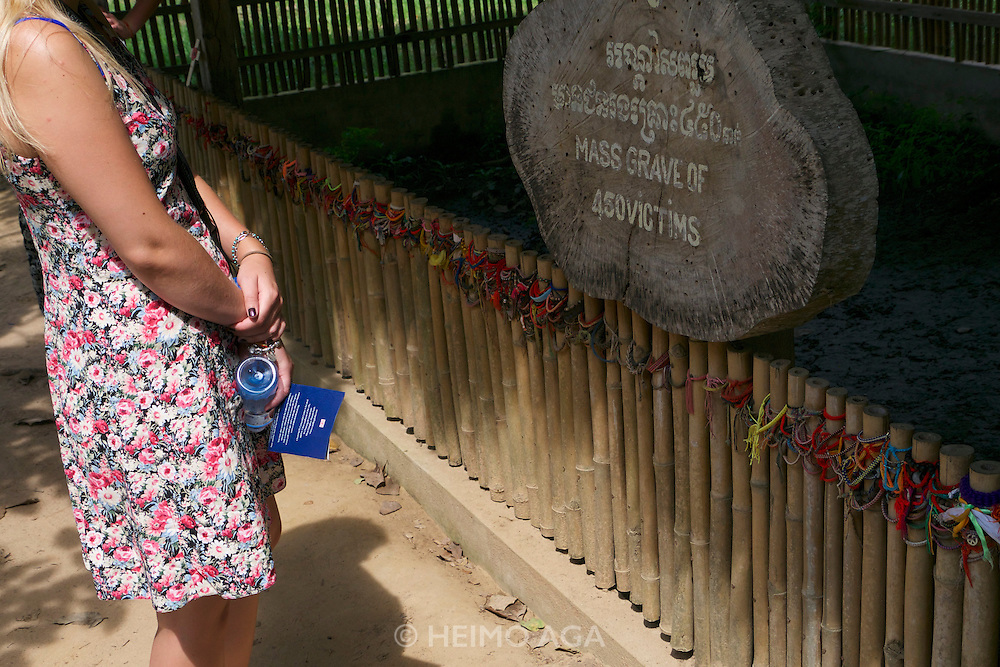 Phnom Penh, Cambodia. Choeung Ek Killing Fields memorial site, a reminder of the genocide committed by the Khmer Rouge. Tourist stopping at a mass grave during the audio tour.