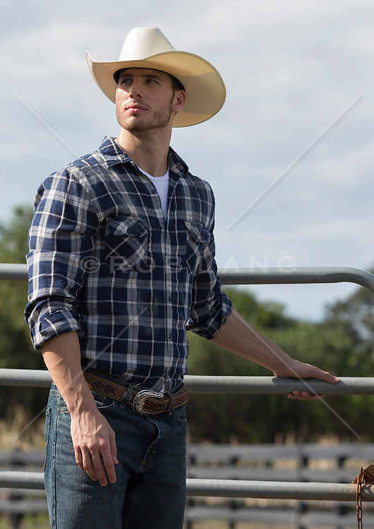 All American Cowboy closing a metal gate on a ranch