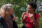 Hunts Point, Bronx, New York - Robin Laverne Wilson, who goes by the stagename Dragonfly, talks about the lyrics of her antconsumerist song with a member of the audience in Hunts Point, the Bronx, New York on Saturday, October 5, 2013. Wilson is from the Bedford-Stuyvesant neighborhood of Brooklyn but travels all over with the Earthalujah Choir.