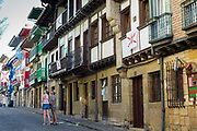 Tourists couple in street scene in alleyway of old town Hondarribia, in Basque Country, Spain