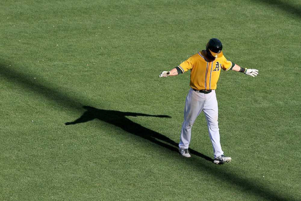 OAKLAND, CA JUNE 13TH: Josh Reddick of the Oakland Athletics appears to be walking the shadow of a stadium light pole as he returns to the dugout during the A's 18 inning win over the New York Yankees.