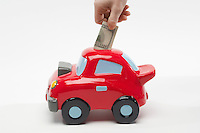 Hand Putting Money in Car Shaped Piggy Bank