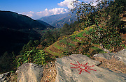 A sun symbol belonging to the Communist Party of Nepal (UML - Unified Marxist Leninist) is seen before elections in a wide landscape of a Himalayan valley in the Gorkha district, one of the 75 districts of central Nepal. Beyond the red-painted sign that has been painted in red on a footpath rock, unavoidable by community passers-by, are fertile terraces where rice and other agricultural crops are growing to sustain villages in these foothills. The light is clear and we can see into the far distance to valleys and hills beyond.