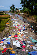 People drying clothing in the rocks near a river in the north coast of São Tomé island.