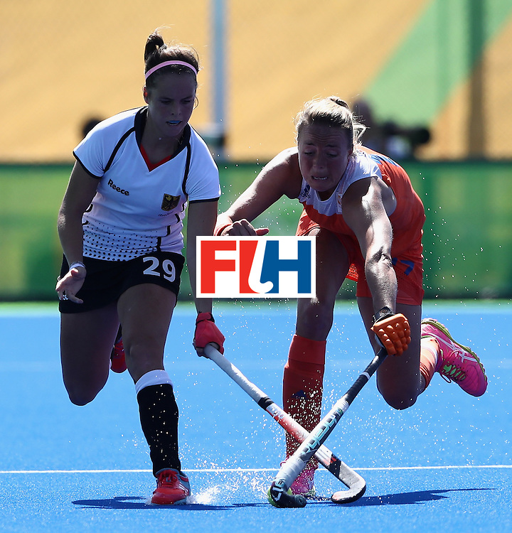 RIO DE JANEIRO, BRAZIL - AUGUST 13:  Pia Sophie Oldhafer (L) of Germany is challenged by Maartj Paumen during the Women's group A hockey match between the Netherlands and Germany on Day 8 of the Rio 2016 Olympic Games at the Olympic Hockey Centre on August 13, 2016 in Rio de Janeiro, Brazil.  (Photo by David Rogers/Getty Images)