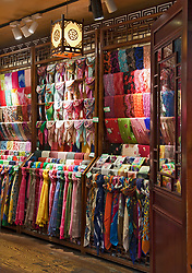 Brilliantly colored silk scarves tempt passing shoppers into this shop on the main street of Ciqikou Old Town, Chongqing, China.