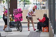 Joe Cox, founder of PMA Bike Ride, passes a slice of pizza to a man in center city, Philadelphia. Saturday June 27, 2017.
