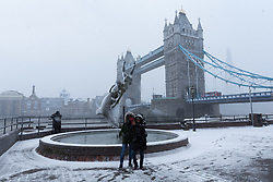 © Licensed to London News Pictures. 27/02/2018. London, UK. Two tourists take a selfie during a heavy snow shower in front of Tower Bridge in London this afternoon. Following the snow shower, the capital saw bright sunshine and clear sky. Photo credit: Vickie Flores/LNP