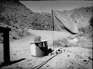 Water is life, especially for undocumented Mexican migrants who enter this desert mountain canyon.  The Border Angels, an NGO that sets out water year round and blankets in winter, set out these relief stations marked by a blue flag beside Interstate 8, Imperial County, California, USA.
