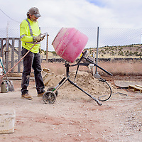 Marc Cooper mixes cement for renovations at the Uranium Capital Speedway in Milan Saturday.