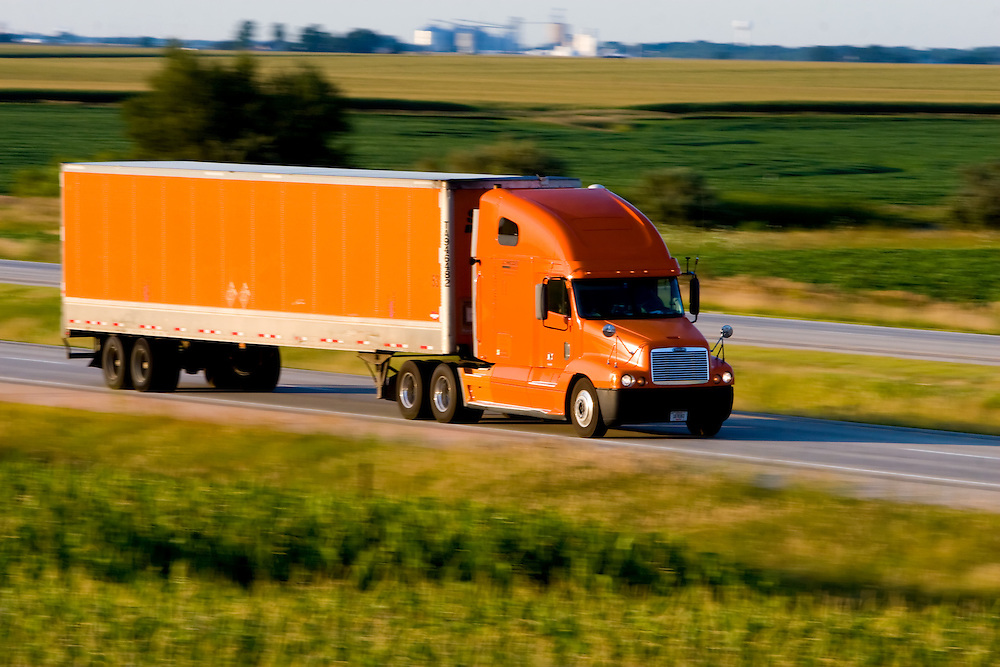 An orange truck and trailer is speeding across the Illinois prairie on I-57 near Gilman, IL.