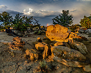 Sandstone boulders catch the last sunlight as a storm recedes beyond a ridge in the plains of northwestern New Mexico, © 2018 David A. Ponton