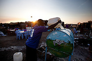 A man pours water for washing hands in Abyei.