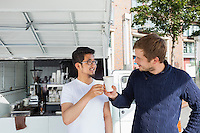 Vendor giving disposable coffee cup to customer against mobile shop