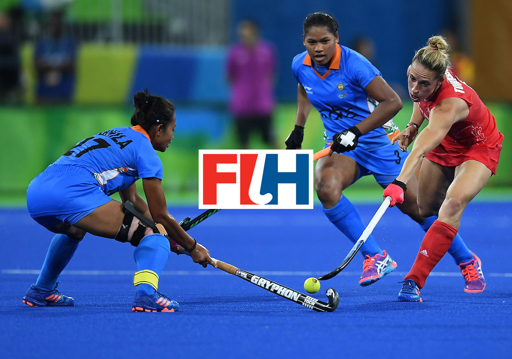 India's Sushila Pukhrambam (L) fights for the ball with Britain's Susannah Townsend as India's Deep Ekka (C) looks on during the women's field hockey India vs Britain match of the Rio 2016 Olympics Games at the Olympic Hockey Centre in Rio de Janeiro on August, 8 2016. / AFP / MANAN VATSYAYANA        (Photo credit should read MANAN VATSYAYANA/AFP/Getty Images)