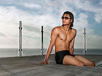 Man in bathing suit sitting at poolside near ocean
