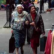 Prinses Juliana winkelend in het centrum van Baarn met een vriendin, in de achtergrond veiligeidsdienst Koninklijk Huis, VDKH