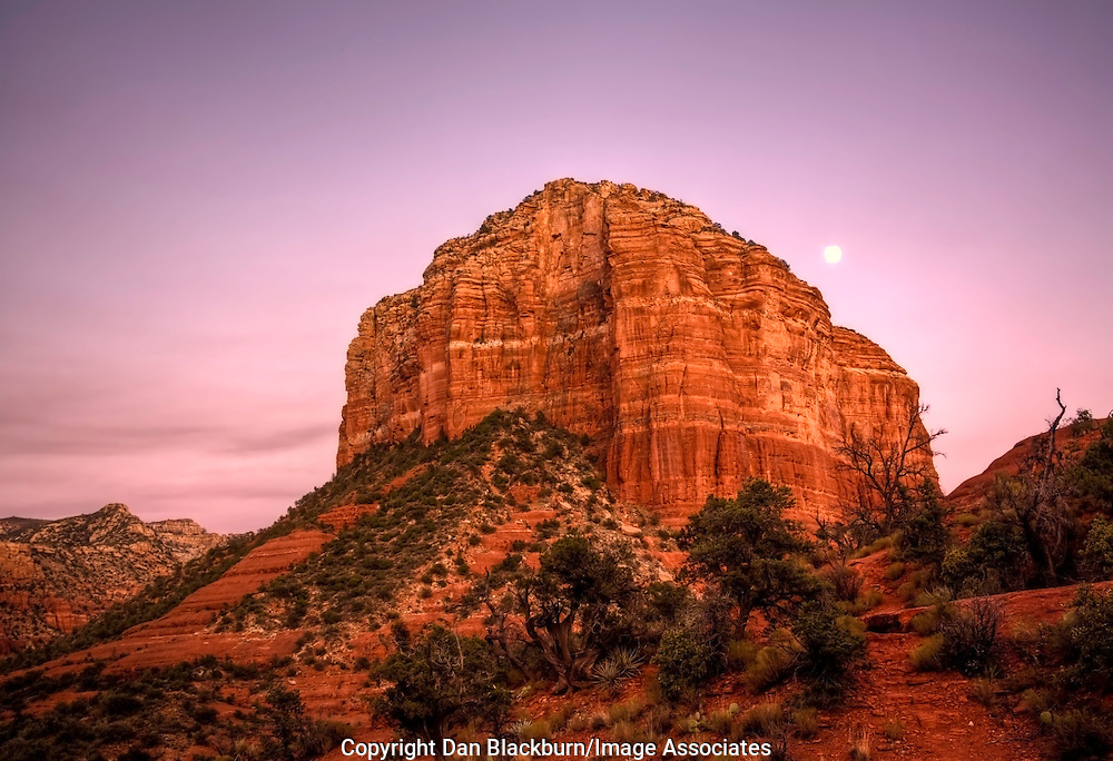 The Moon Rises over the Shoulder of Courthouse Butte in Sedona, Arizona, as Sunset paints the Sky and Butte a Deep Red Orange.