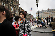 Asian tourist in Paris with homeless man sleeping in the background