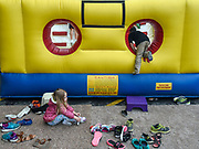 Three-year-old Olivia Dumas puts her shoes back on while other kids climb into the bounce house obstacle course during the second annual Coborn's Kickoff to Summer event on Saturday in the Coborn's parking lot in Mitchell. (Matt Gade / Republic)
