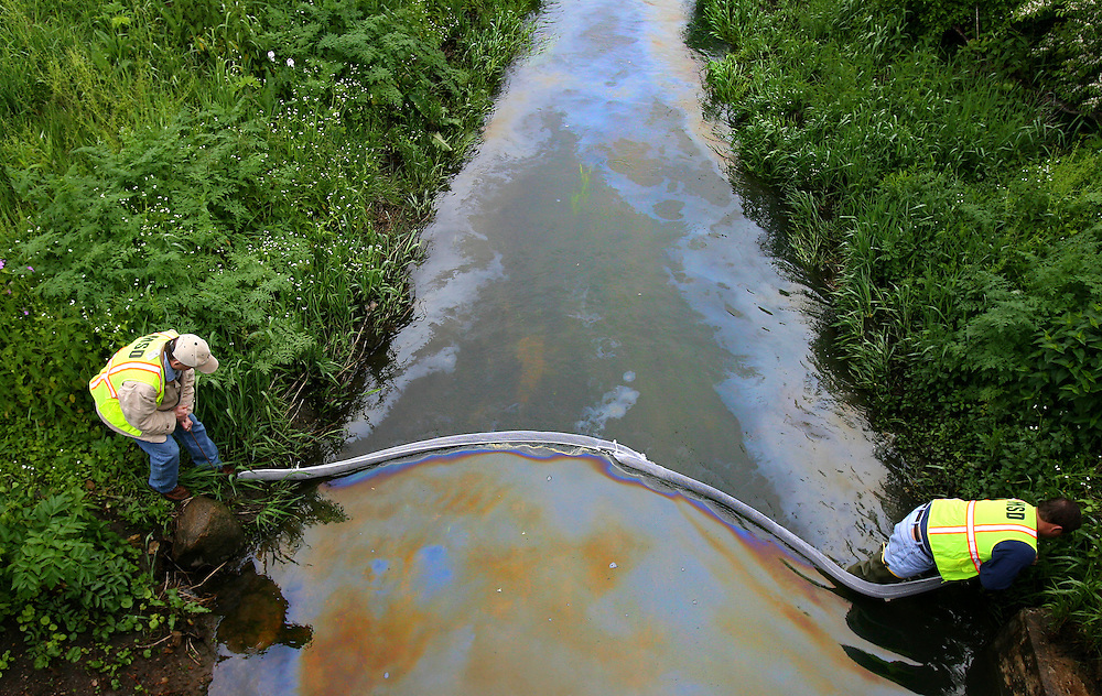 contain an oil spill using an absorbent barrier that collects 50 pounds of oil each. The spill started close to Ball State Monday afternoon..Photo by Chris Bergin....